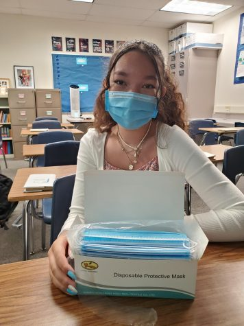 Freshman student Talania Wilson poses with masks indoors.