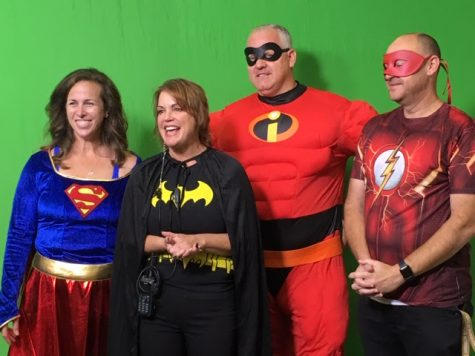 Ms. Surfas (lft.) and Dr. Hodgson (3rd from left) appearing on the announcements in costume in 2019.
